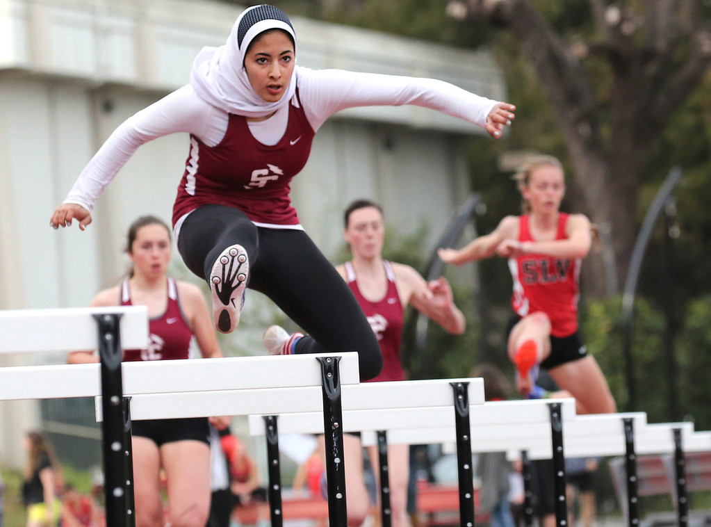 . Santa Cruz High\'s Nora Griffith takes the first hurdle en route to a victory in the 300 meter hurdles at a home track and field meet against San Lorenzo Valley Thursday. (Shmuel Thaler -- Santa Cruz Sentinel)