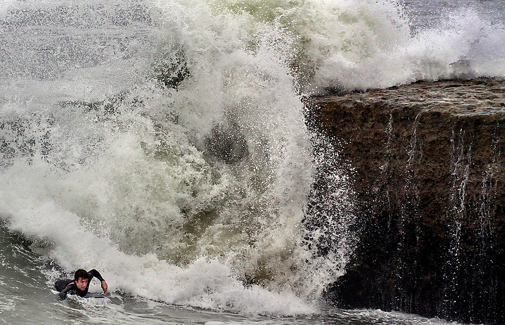 . A boogie boarder paddles into the surf as a large wave crashes into Sunny Cove near the end of 17th Avenue in Santa Cruz, California on Wednesday September 6, 2017.