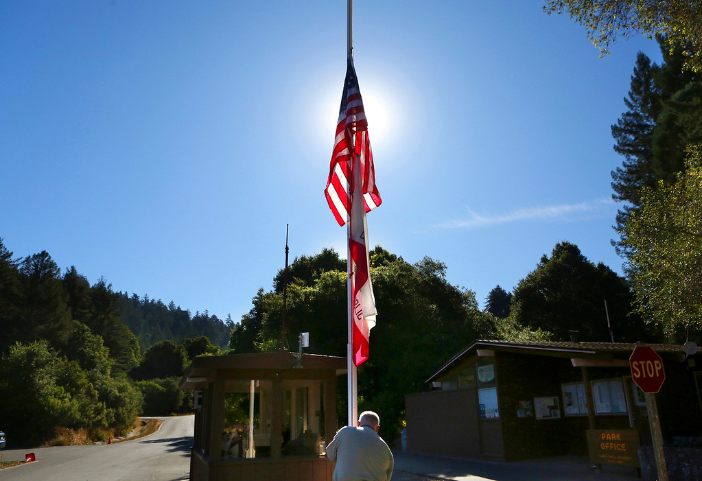 . Park aide Ted Lodge lowers the flag at the entrance to Henry Cowell Redwoods State Park in Felton, Calfiornia on October 4, 2017 to half-staff Wednesday morning as the nation mourns the victims of the shooting tragedy in Las Vegas. Flags will continue to fly at half-staff through Friday.