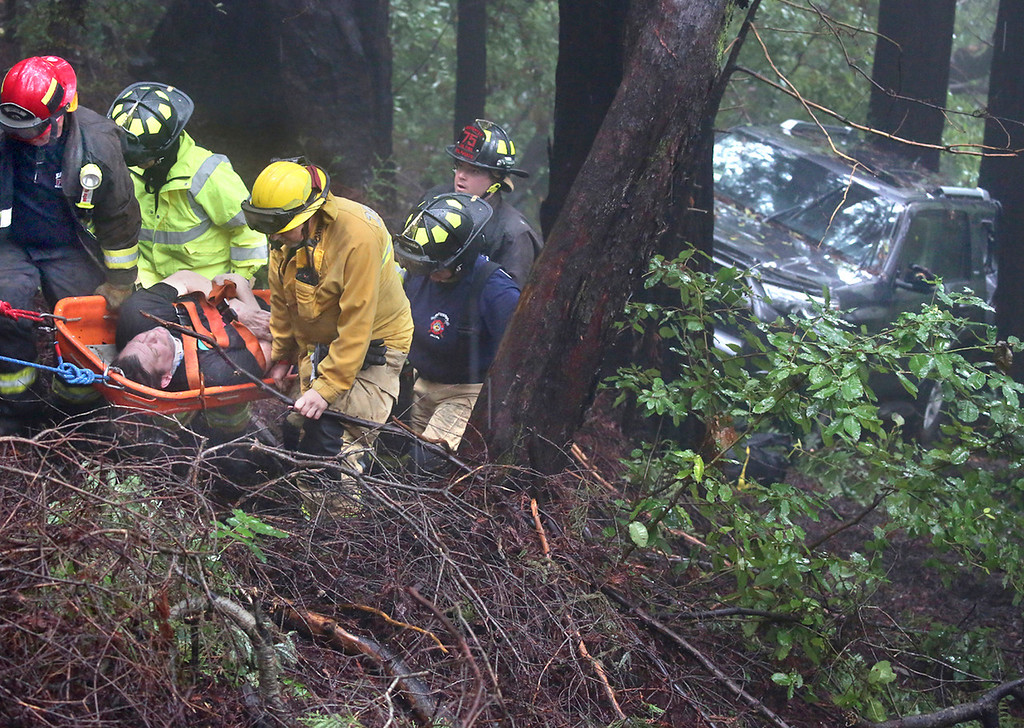 . Zayante firefighters use a Stokes basket to bring a Scott Hall, 50, of Felton, up a ravine to safety after he drove his Toyota 4Runner down an embankment off of Lake Blvd. in Lompico Wednesday morning. Hall was transported by ambulance for medical treatment to Dominican Hospital where he was also arrested on suspicion of driving under the influence. (Shmuel Thaler -- Santa Cruz Sentinel)