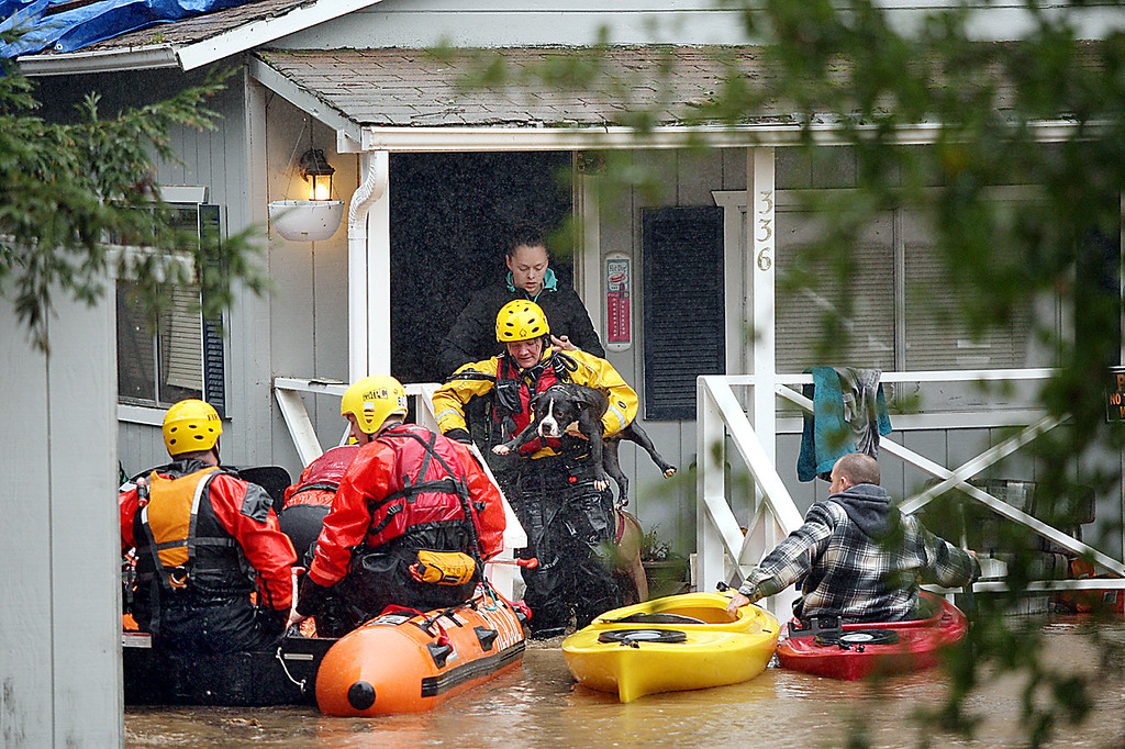. Ben Lomond Firefighters rescue Rachel Turner and her dogs from their flooded home on Old Covered Bridge Raod in Felton Tuesday morning when the San Lorenzo River flooded Felton Grove and the surrounding neighborhood.  (Dan Coyro -- Santa Cruz Sentinel)