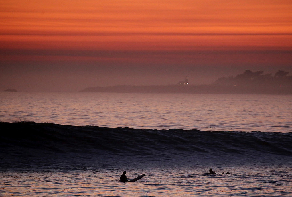 . Two surfers work to get in a last ride as a large swell pours in to Moran Lake Beach near Pleasure Point in Santa Cruz, California as the sunset paints the sky a fiery orange above Lighthouse Point in the distance on Wednesday December 13, 2017.