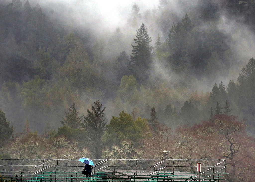 . Low lying clouds and fog drape the Santa Cruz Mountains over Felton as a soccer fan tries to keep dry in the visiting stands as the San Lorenzo Valley high School girls play Santa Cruz High. The teams played to a 1-1 tie on the rain-soaked pitch. (Shmuel Thaler -- Santa Cruz Sentinel)