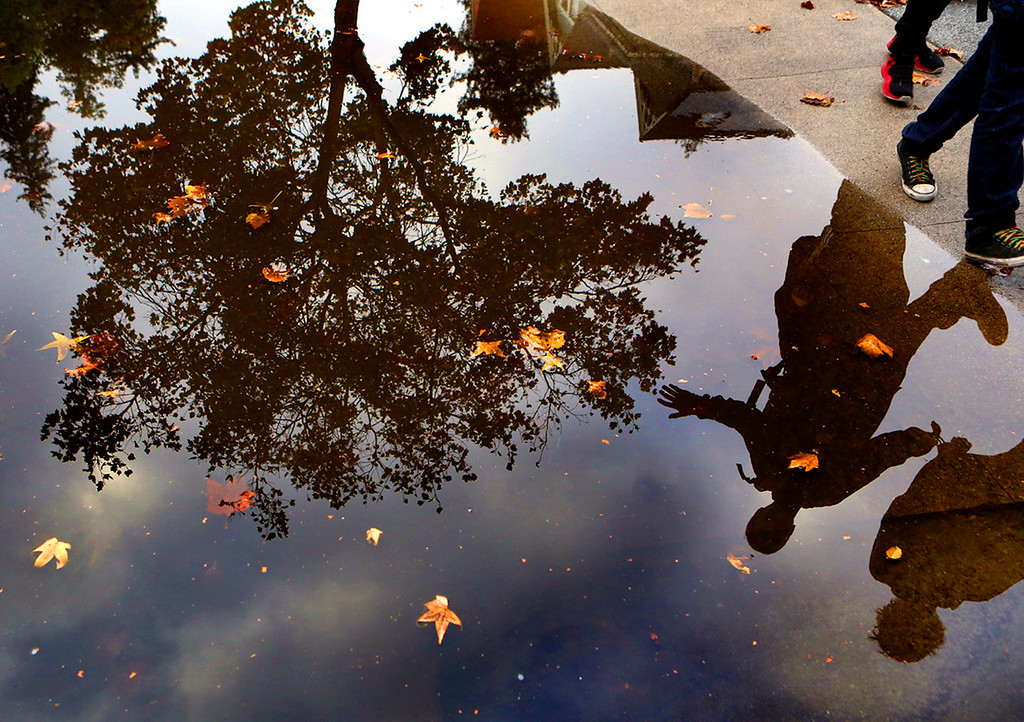 . Students heading home from Mission Hill Middle School are reflected in a puddle along Walnut Avenue in Santa Cruz Thursday afternoon