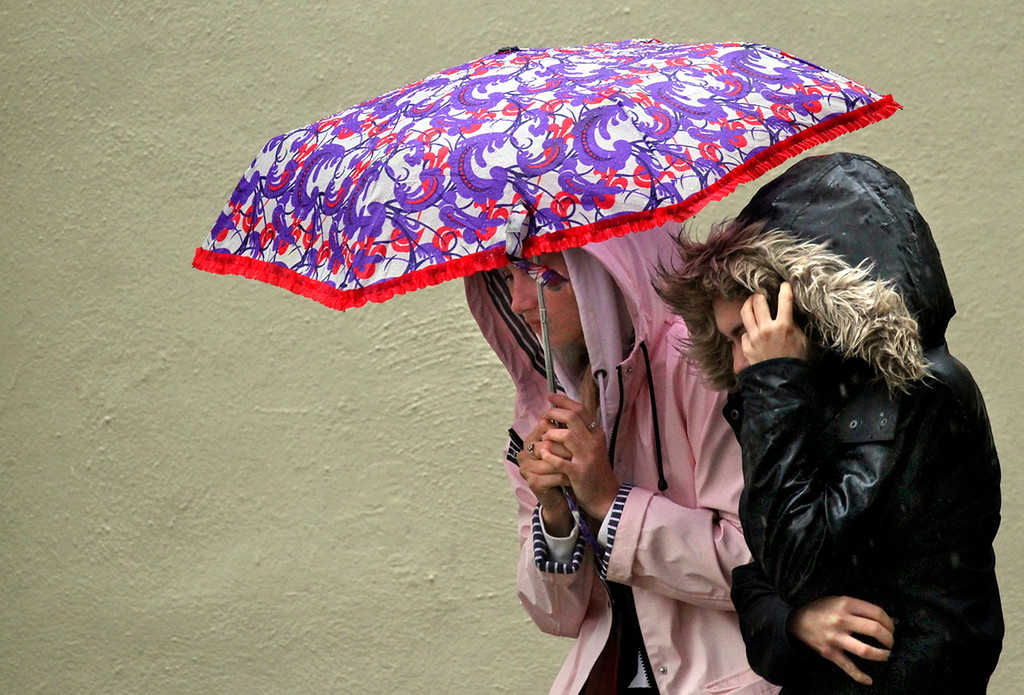 . Two women huddle against the rain and wind along Pacific Avenue in downtown Santa Cruz Thursday afternoon. (Shmuel Thaler -- Santa Cruz Sentinel)
