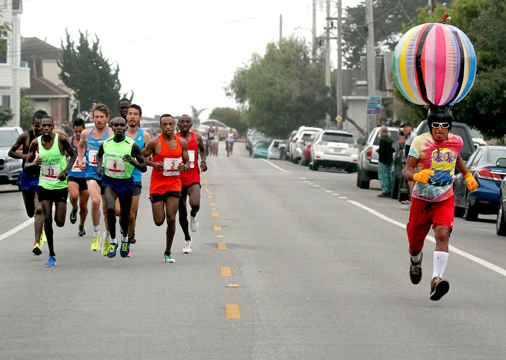 . Reve Fuse, right, has a ball as he runs with the race leaders up Seabright Avenue near the 2-mile mark of the 45th annual Wharf to Wharf Race Sunday. (Shmuel Thaler -- Santa Cruz Sentinel)