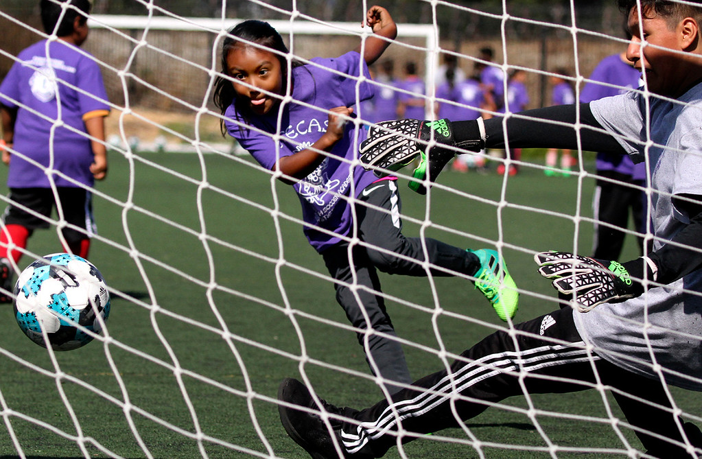 . Samantha Alvarado, 7, finds the net past coach Pedro Melendez at Aztecas Youth Soccer Academy Soccer Camp at Pajaro Park Thursday. The Aztecas Youth Soccer Academy uses soccer to reclaim the lives of at-risk Latino youth who struggle with gangs, violence and poverty in Santa Cruz County and the Pajaro Valley. Players develop the life skills to thrive on and off the field: with each other, with family, and with community. All the male coaches at the camp, now in its third year, have had interactions with the probation department and are turning their lives around, and the female coaches are all players on Santa Cruz County high school teams. Nearly 150 youth from the Watsonville and Pajaro areas participated for this year in two one-week sessions, while the camp still had a waiting list of 40. The $10 fee for the camp included a t-shirt, soccer ball and bag, a water bottle along with snack and a lunch. The camp is made possible through the generosity of Freedom and San Martin Lions Clubs, Sunridge Farms along with a number of other Lions Clubs. Coach Meledez in the photo will be an incoming freshman at Watsonville High School in August. (Shmuel Thaler -- Santa Cruz Sentinel)