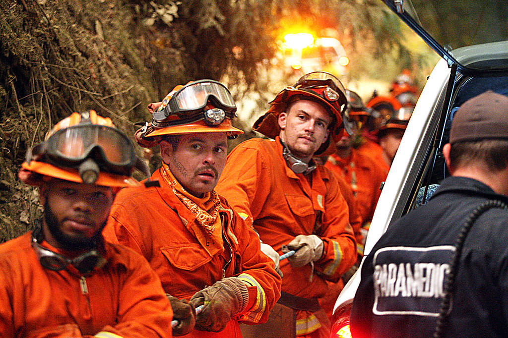 . California Department of Corrections and Rehabilitation firefighting inmates use a rope to pull their Cal Fire colleagues up a near-vertical canyon wall after battling the Bear Fire off Bear Creek Raod early Tuesday. (Dan  Coyro -- Santa Cruz Sentinel)