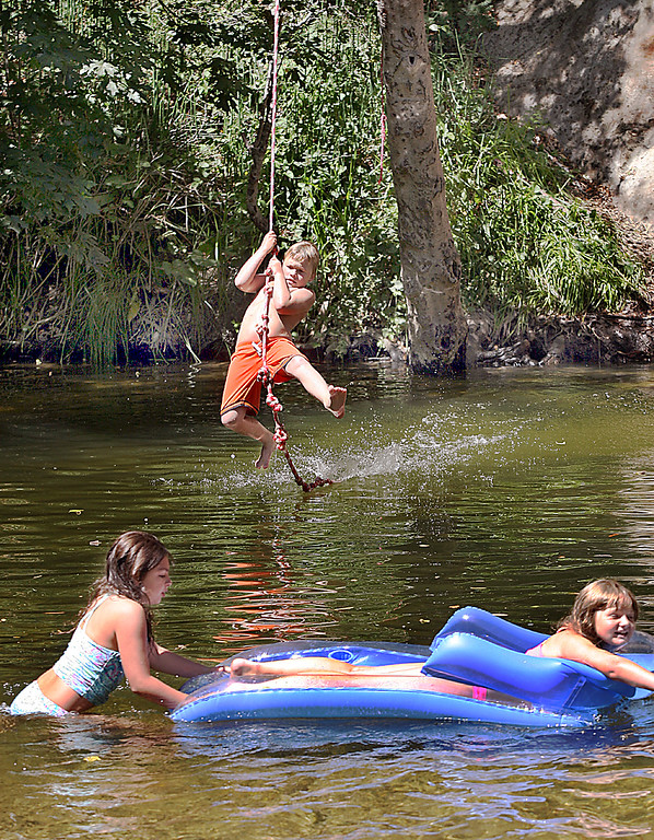 . A young boy swings in to make a splash landing Wednesday at Junction Park, Boulder Creek\'s popular swimming hole along the San Lorenzo River on a hot day.  (Dan  Coyro -- Santa Cruz Sentinel)