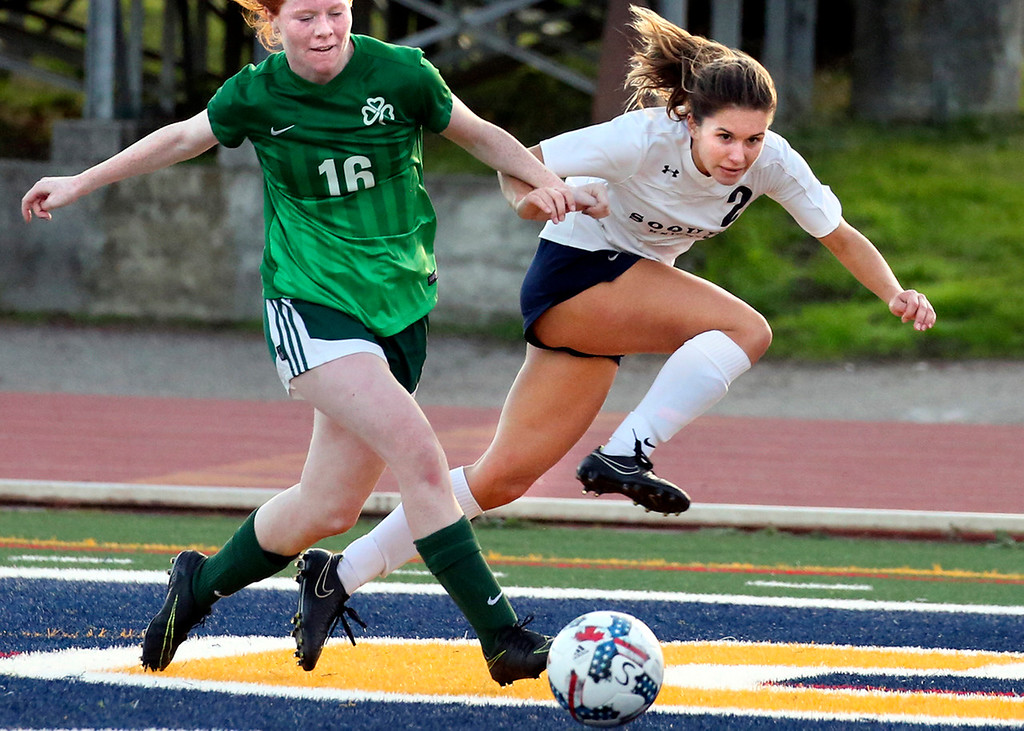 . Soquel junior Raylene Allen, right, kicks the ball toward the goal while tangling with Sacred Heart Cathedral\'s Rhea Chan during the first half of the Knights\' home match Thursday. (Shmuel Thaler -- Santa Cruz Sentinel)
