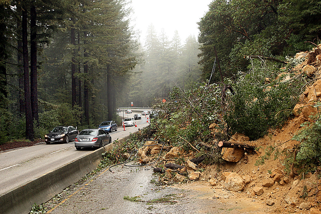 . Vast muslide covers both northbound lanes of Highway 17 north of Vine Hill Road Monday.  At left, northbound traffic is diverted to the fast lane of southbound Highway 17.  The slide injured Channel 7 videographer and Santa Cruz resident Ian Babcock, whose van was crushed by the slide as Babcock was driving to San Jose early Monday monring.  (Dan Coyro -- Santa Cruz Sentinel)