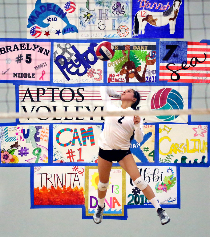 . Aptos High libero Trinita Barrios jump serves in front of a wall of spirit posters during the Mariners\' first home match of the season in Aptos, California on Thursday August 24, 2017 against Monte Vista Christian School. MVC won the match 3-1.