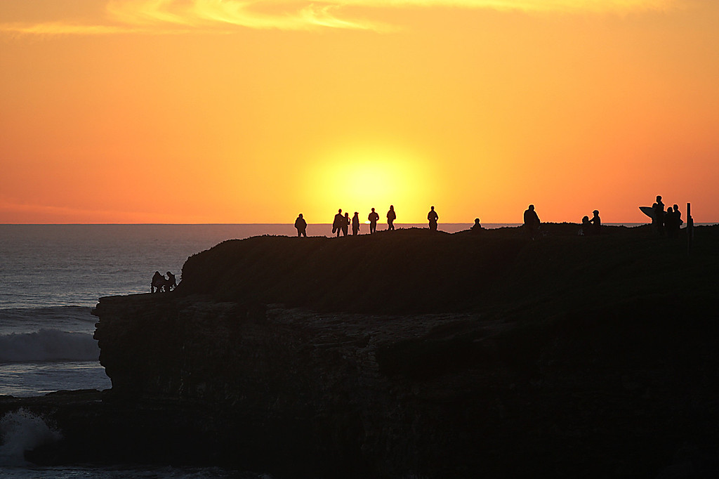 . Sunset seekers gather on West Cliff to watch the end of the day disappear over the horizon.  Santa Cruz has been treated to a series of golden sunsets over the past week.  (Dan Coyro -- Santa Cruz Sentinel)