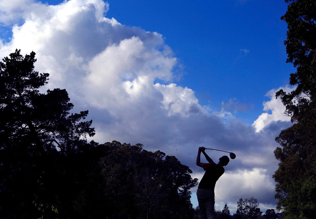 . A dramatic cloudscape rises above San Lorenzo Valley High golfer Taj Yanez as he tees off on the ninth hole at Delaveaga Golf Course Tuesday during SLV\'s match against Scotts Valley. Scotts Valley won the match 204-234. (Shmuel Thaler -- Santa Cruz Sentinel)