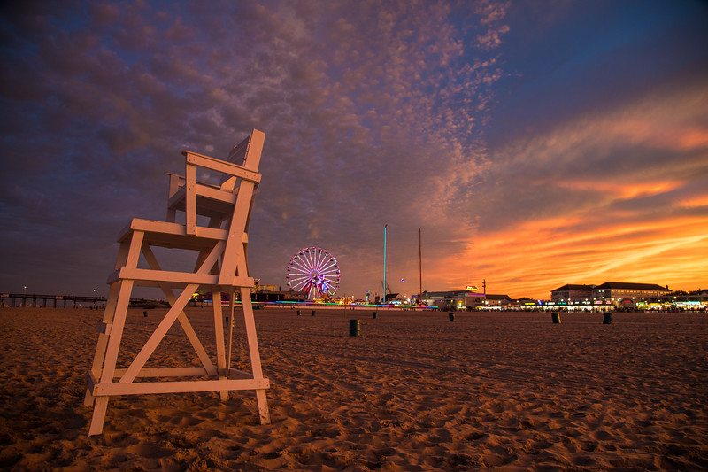 A view from the beach of the sun setting over Ocean City, Maryland and the famous ferris wheel on the boardwalk.