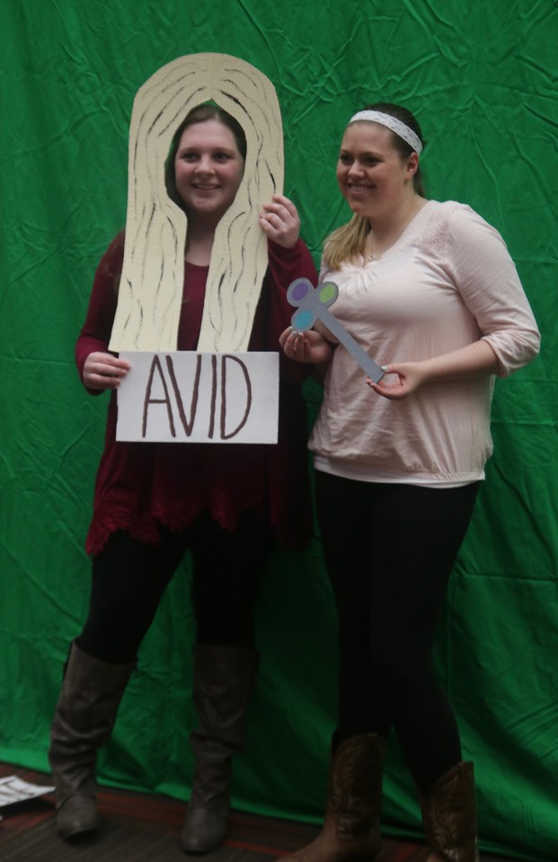 Students got their pictures taken with book related props at the green screen photo booth which will place the book cover background behind them.