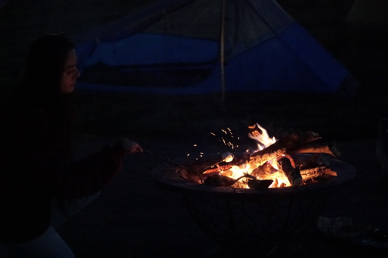 Shelley Vega roasts a marshmallow while camping on the quad.