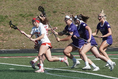 Amanda Steinmuller carries the ball away from Furman players