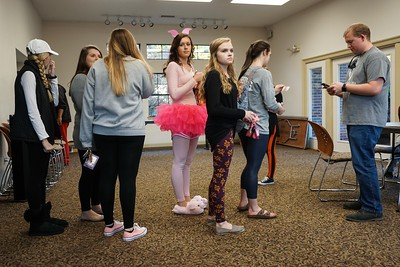 Students stand in line on Halloween, excited for a sweet treat.
