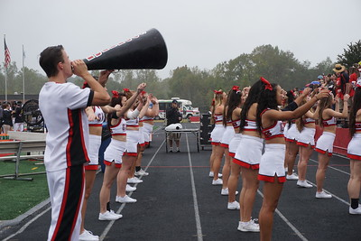 The cheerleaders hype up the crowd with a cheer.