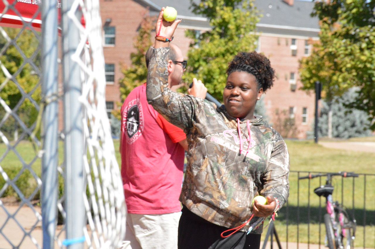 "Jada Robbs throws a tennis ball to try and dunk a professor at the ""Dunk 'N' Donuts"" event in front of Tucker."