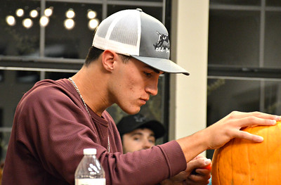 Carey Spratln is focused on his pumpkin, carving it to perfection.