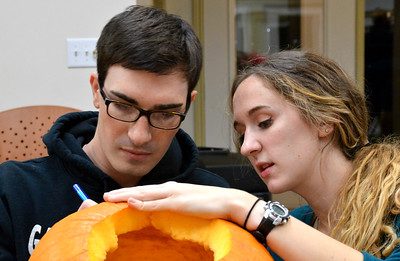 Dalton Meyers and Laura Denman work together to trace their pumpkin masterpiece.