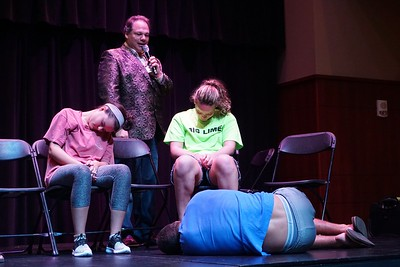 The hypnotist looks at a deeply hypnotized volunteer who just fell out of his chair on the floor.