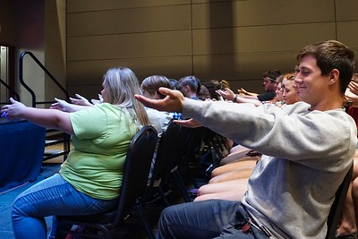Students close their eyes and listen to the hypnotist, not realizing they are all slowly dropping one of their arms.
