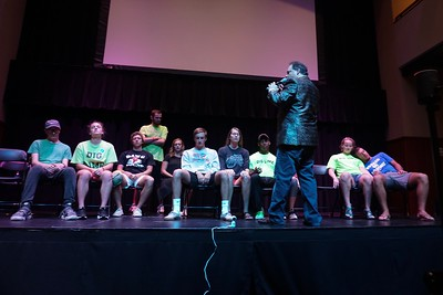 The hypnotist transitions the group to the next part of the show. Unhypnotized volunteers left the stage.