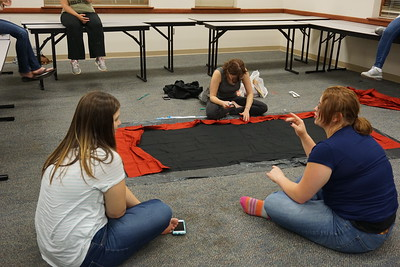 Lexi Keller analyzes the fabric of the banner while Katie Linker and Alexis Starnes talk.