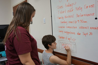 Lisa Martinat and Emily Anne Grace discussing designs for the Joyful Hands banner at the whiteboard