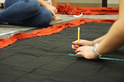 A Joyful Hands member carefully begins drawing the design onto the fabric in pencil