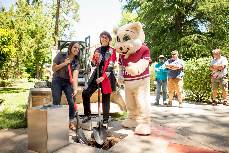 (from left to right) Alisha Sharma, Willie the Wildcat, and President Gayle Hutchinson smile in front of Kendall Hall during the Class of 2017 time capsule burial on Tuesday May 2, 2017 in Chico, Calif. Graduating students placed symbolic items into the time capsule, which is buried and will not be reopened until the year 2067. <br /> (Jessica Bartlett/ Photographer)
