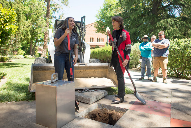 Alisha Sharma (left) and President Gayle Hutchinson (right) smile in front of Kendall Hall during the Class of 2017 time capsule burial on Tuesday May 2, 2017 in Chico, Calif. Graduating students placed symbolic items into the time capsule, which is buried and will not be reopened until the year 2067. <br /> (Jessica Bartlett/ Photographer)