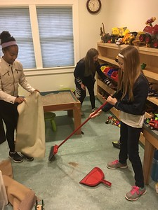 From left to right: Sophia D., Julia P., and Eliska J. (all '23) clean and organize the sand play room at the Dougy Center, an organization that provides support to grieving children and families.