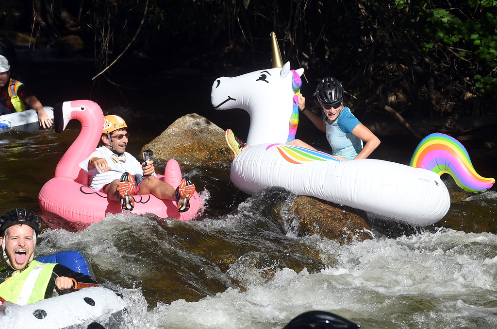 . Charles Garabedian, left, and his wife,  Laura Zaunbrecher, on the unicorn, handle the rocks in Boulder Creek  during the 10th Annual Tube to Work Day in Boulder on Friday.For more photos and videos, go to dailycamera.com.  Cliff Grassmick  Staff Photographer July 14, 2017