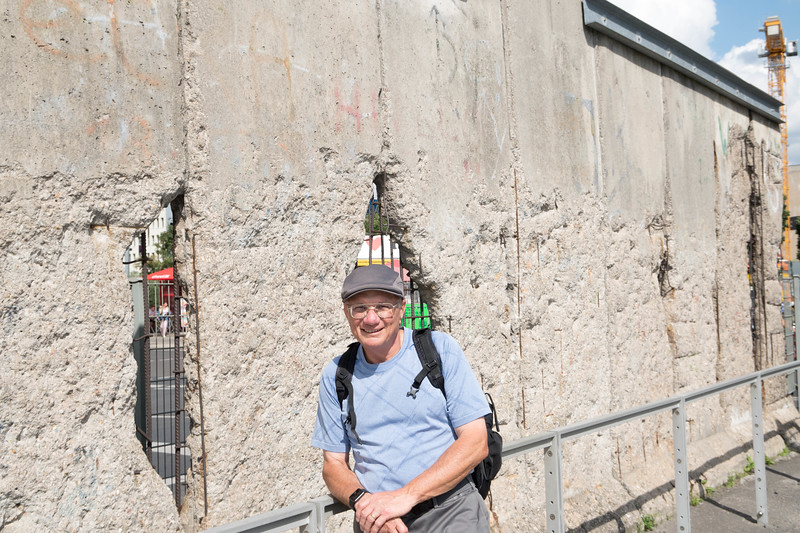 Standing next to one of the few remaining sections of the Berlin Wall