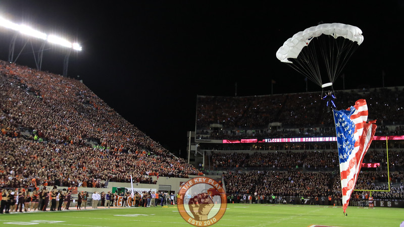 A parachute team flies into Lane Stadium after the national anthem carrying Virginia Tech and American flags. (Mark Umansky/TheKeyPlay.com)