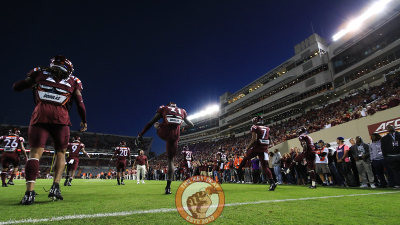 The Hokies warm up on the field in front of hundreds of recruits and their familes as the sun finishes setting over Lane Stadium. (Mark Umansky/TheKeyPlay.com)