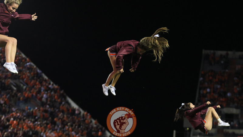 Virginia Tech cheerleaders flip through the air during a media timeout. (Mark Umansky/TheKeyPlay.com)