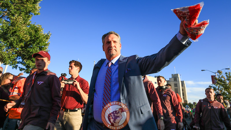 Bud Foster holds a bag of smarties up as he waves to the crowd during the walk to the locker rooms. (Mark Umansky/TheKeyPlay.com)