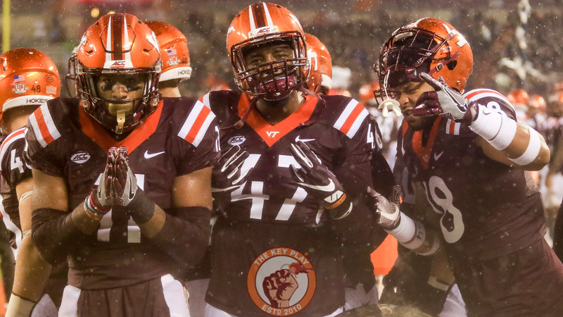 Darius Fullwood (47), Houshun Gaines (11) and Raymon Minor (18) pose for a photo next to a heater behind the Virginia Tech bench. (Mark Umansky/TheKeyPlay.com)