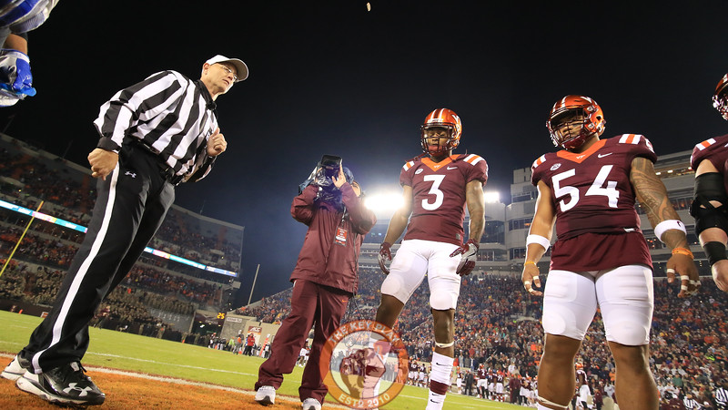 Greg Stroman (3) and Andrew Motuapuaka (54) watch as referee Jeff Flanagan executes the coin toss before kickoff. (Mark Umansky/TheKeyPlay.com)