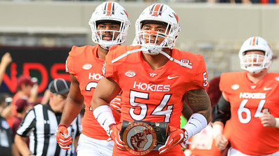 Andrew Motuapuaka carries in the lunchpail with the rest of the game's captains before the rest of the team enters the field. (Mark Umansky/TheKeyPlay.com)