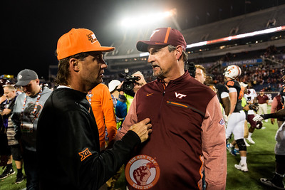Mike Gundy (left) and Bud Foster chat after the Camping World Bowl between Virginia Tech and Oklahoma State in Orlando, Fl., Thursday, Dec. 28, 2017. (Special by Cory Hancock)