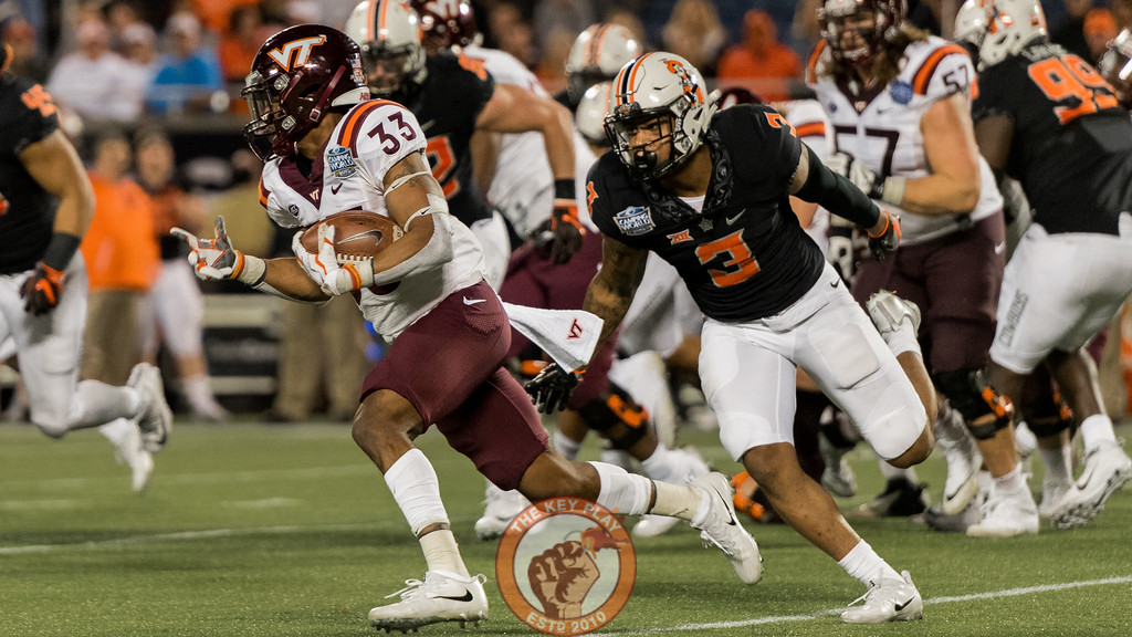 Deshawn McClease (33) runs past Kenneth Edison-McGruder (3) in the Camping World Bowl between Virginia Tech and Oklahoma State in Orlando, Fl., Thursday, Dec. 28, 2017. (Special by Cory Hancock)