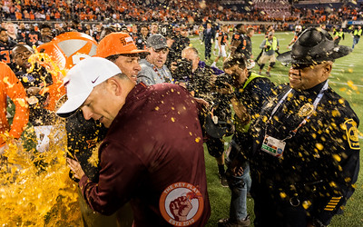 Justin Fuente (front) and Mike Gundy are doused in orange Gatorade during their post-game handshake at midfield after the Camping World Bowl between Virginia Tech and Oklahoma State in Orlando, Fl., Thursday, Dec. 28, 2017. (Special by Cory Hancock)