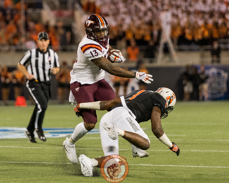 Jalen Holston (13) shoves aside Calvin Bundage (1) in the Camping World Bowl between Virginia Tech and Oklahoma State in Orlando, Fl., Thursday, Dec. 28, 2017. (Special by Cory Hancock)