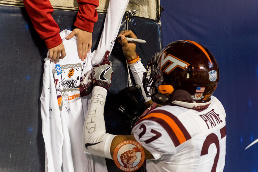 Shawn Payne signs a fan's sleeve after the Camping World Bowl between Virginia Tech and Oklahoma State in Orlando, Fl., Thursday, Dec. 28, 2017. (Special by Cory Hancock)